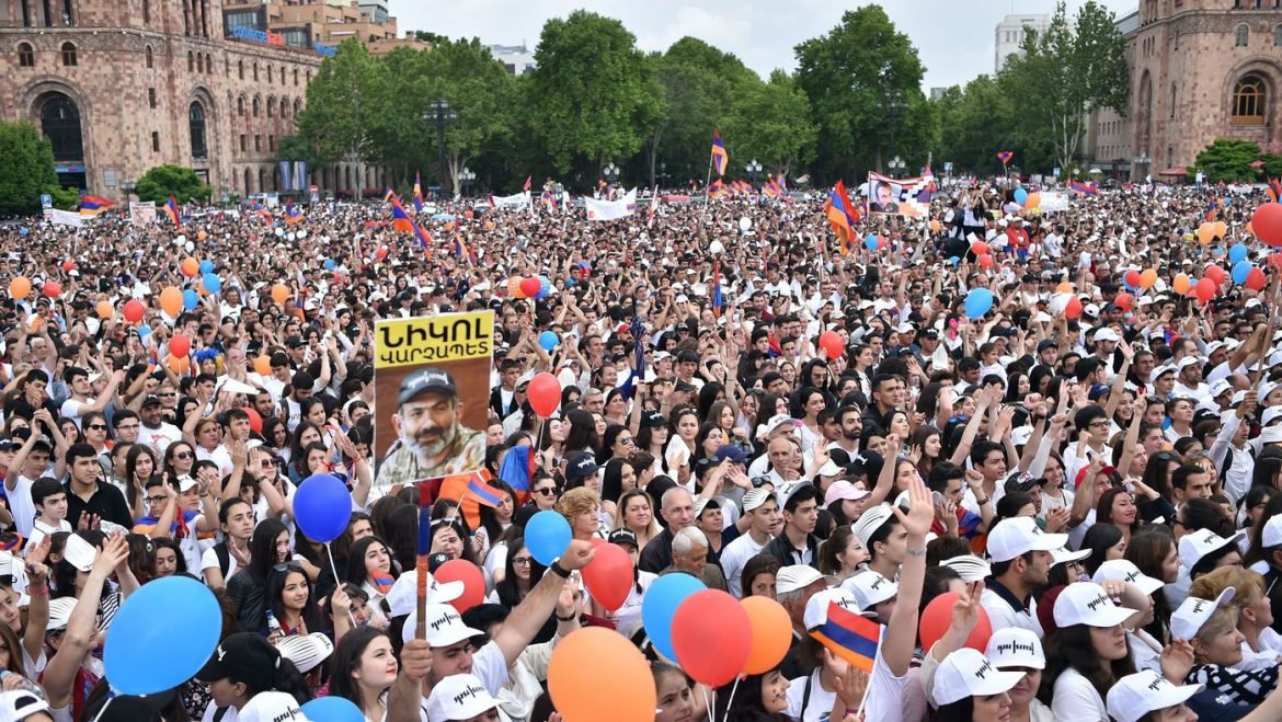 Demonstrators gather in Yerevan's Republic Square on Tuesday, as one supporter holds up a sign showing Pashinyan, with his trademark camouflage T-shirt and black cap.