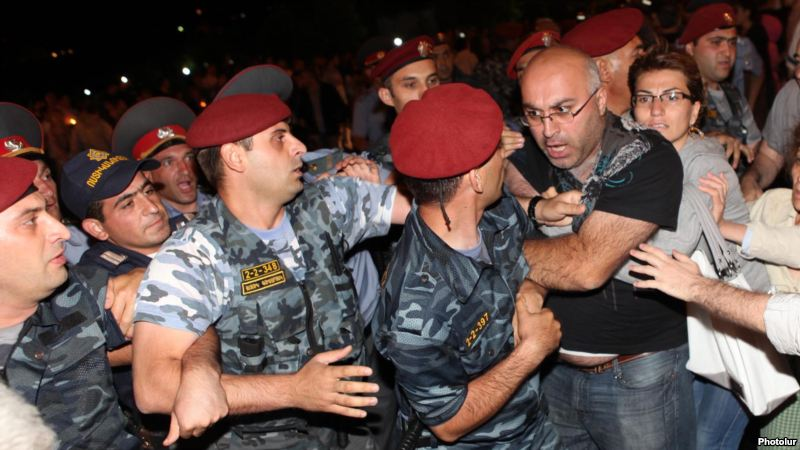 Protesters clash with riot police near the Harsnakar restaurant in Yerevan