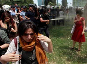 In a photo that has been adopted by protesters as a symbol of their struggle, a Turkish riot policeman uses tear gas against a woman during a rally in Taksim Square in central Istanbul on May 28.