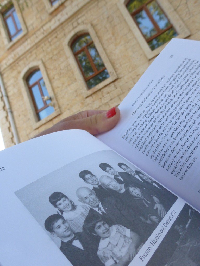 Holding book with photo of Babi Hovakim and Mami Chnkuhi with grandchildren (Fresno, 1972), while standing in front of school-turned orphanage in Ordu, where Mami Chnkuhi lived as a little girl during/after Genocide.