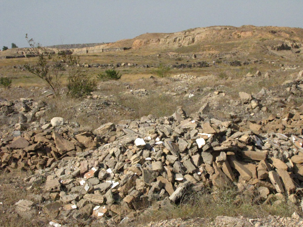 Construction trash dumped at Garmir Blur Urartian archaeological site, in back are foundations of dwellings, citadel on top of hill has been excavated