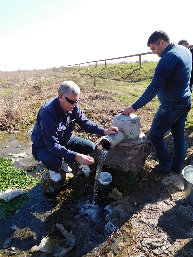 Mark Anderson, Director of the USGS South Dakota Water Science Center, demonstrates how to collect a stable isotope sample from a flowing well near Sis, Armenia