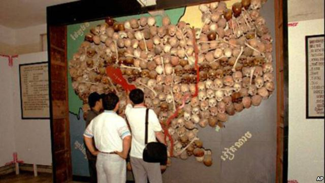 Visitors to Toul Sleng, officially known as S-21 prison look at a wall of sculls and bones made into a map of Cambodia
